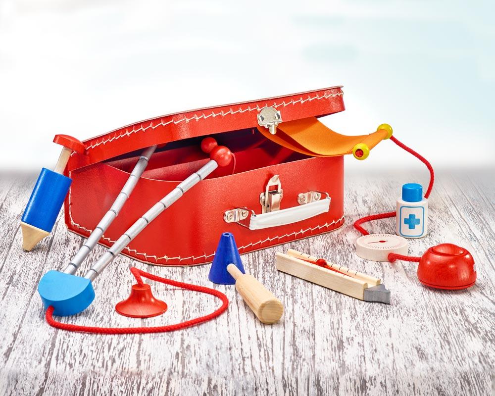 Holz roter Arztkoffer offen für Kinder mit Stethoskop, Fieberthermometer, Blutdruckmesser, Spritzer und Klopghammer