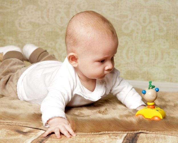 Baby mit Zoolini Giraffe Holzspielzeug von Selecta